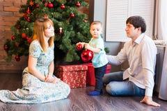 El pequeño bebé que adorna un árbol de navidad juega Días de fiesta, regalo, y concepto del Año Nuevo Imágenes de archivo libres de regalías
