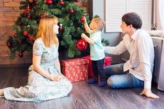 El pequeño bebé que adorna un árbol de navidad juega Días de fiesta, regalo, y concepto del Año Nuevo Imagenes de archivo