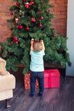 El pequeño bebé que adorna un árbol de navidad juega Días de fiesta, regalo, y concepto del Año Nuevo Fotos de archivo libres de regalías