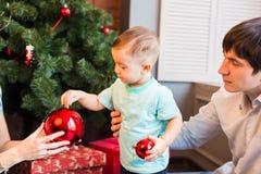 El pequeño bebé que adorna un árbol de navidad juega Días de fiesta, regalo, y concepto del Año Nuevo Imagen de archivo libre de regalías