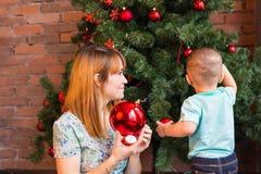 El pequeño bebé que adorna un árbol de navidad juega Días de fiesta, regalo, y concepto del Año Nuevo Imagen de archivo