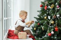 El pequeño bebé que adorna un árbol de navidad juega Días de fiesta, regalo, y concepto del Año Nuevo Fotografía de archivo