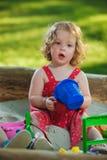 El pequeño bebé que juega los juguetes en arena Imagenes de archivo