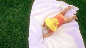 El pequeño bebé que pone en la toalla en la hierba, remata abajo de la visión almacen de metraje de vídeo