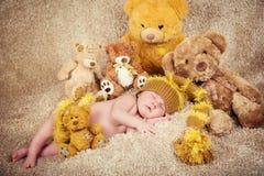 El pequeño bebé recién nacido en un casquillo hecho punto que duerme cerca de osos de peluche juega Imagen de archivo