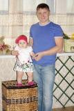 El pequeño bebé se coloca en el mimbre grande y su padre feliz Fotos de archivo