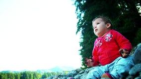 El pequeño bebé se está sentando en la orilla del río almacen de video
