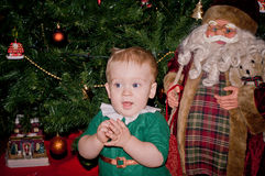 El pequeño bebé se sienta debajo del árbol de navidad adornado con Papá Noel Fotografía de archivo