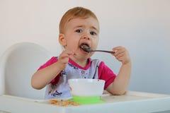 El pequeño bebé sonriente se sienta en el highchair y come las gachas de avena en la placa Fotografía de archivo libre de regalías