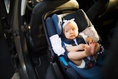 El pequeño bebé sujetó con la correa de la seguridad en asiento de carro de la seguridad Foto de archivo libre de regalías