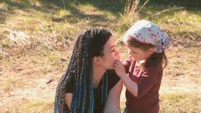 El pequeño beso lindo de la muchacha y abraza a su mamá Caminata en parque almacen de video