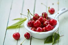 El pequeño cacillo llenó de las cerezas dulces rojas maduras Fotos de archivo