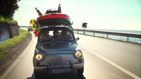 El pequeño coche llenó de los juguetes de los niños, camino hacia la playa almacen de video