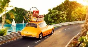 El pequeño coche retro lindo con las maletas y la bicicleta en el top va por el camino Imagen de archivo libre de regalías