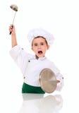 El pequeño cocinero enojado del muchacho amenaza Fotografía de archivo