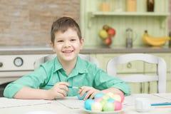 El pequeño colorante rubio del muchacho del niño eggs para el día de fiesta de Pascua en cocina nacional Foto de archivo