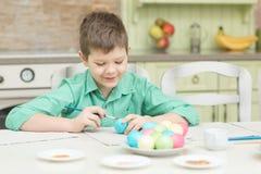 El pequeño colorante rubio del muchacho del niño eggs para el día de fiesta de Pascua en cocina nacional Imagenes de archivo