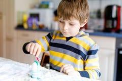 El pequeño colorante rubio del muchacho del niño eggs para el día de fiesta de Pascua en cocina nacional, dentro Fotos de archivo libres de regalías