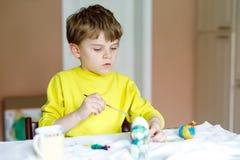 El pequeño colorante rubio del muchacho del niño eggs para el día de fiesta de Pascua en cocina nacional, dentro Imagen de archivo