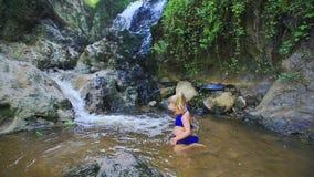 El pequeño comienzo de la muchacha a nadar en corriente riega por la cascada metrajes