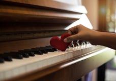 El pequeño corazón rojo fue puesto en llaves del piano por la mano humana, tono ligero caliente, reflexión de la luz del sol es b fotos de archivo libres de regalías