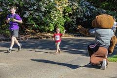 El pequeño corredor del muchacho agita en la mascota de la universidad durante el funcionamiento 5K foto de archivo libre de regalías