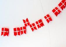 El pequeño danés señala la guirnalda por medio de una bandera en el blanco agrietado Imagen de archivo libre de regalías