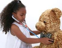 El pequeño doctor que juega adorable To A Teddy Bear sobre blanco Fotografía de archivo libre de regalías