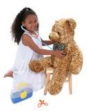 El pequeño doctor que juega adorable To A Teddy Bear sobre blanco Fotos de archivo