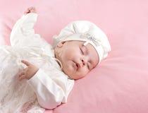El pequeño dormir del bebé vestido en el juego blanco Fotografía de archivo