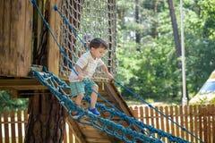 El pequeño escalador toma el puente de cuerda El muchacho tiene tiempo de la diversión, niño que sube en día de verano caliente s Foto de archivo