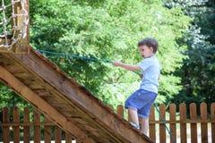 El pequeño escalador toma el puente de cuerda El muchacho tiene tiempo de la diversión, niño que sube en día de verano caliente s Foto de archivo libre de regalías