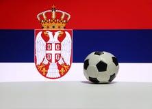 El pequeño fútbol en el piso blanco con la imagen blanca del color azul y rojo, del águila y de la corona de la nación servia señ fotos de archivo