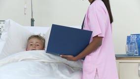 El pequeño hablar paciente con una enfermera en hospital almacen de metraje de vídeo