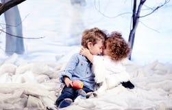 El pequeño hermano besa a una hermana más joven Foto de archivo