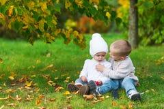 El pequeño hermano cuida para la hermana del bebé en el parque del otoño Fotos de archivo