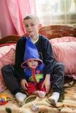 El pequeño hermano y la hermana se están sentando en la cama en el cuarto fotografía de archivo