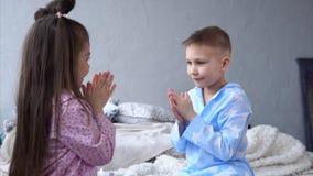 El pequeño hermano y la hermana se vistieron en juego hecho en casa del juego de los pijamas en sus manos almacen de metraje de vídeo