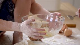 El pequeño hijo ayuda a la madre a implicar los ingredientes en la pasta en un cuenco transparente en cocina almacen de video