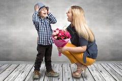 El pequeño hijo da a su madre querida un ramo hermoso de rosas rosadas Primavera, concepto de vacaciones de familia Día del ` s d Imagen de archivo