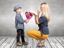 El pequeño hijo da a su madre querida un ramo hermoso de rosas rosadas Primavera, concepto de vacaciones de familia Día del ` s d Foto de archivo