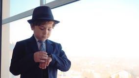 El peque?o hombre de negocios del muchacho en traje y sombrero en su oficina est? mirando la ventana y entonces los relojes para