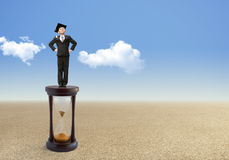 El pequeño hombre de negocios se coloca en un reloj de arena Imagen de archivo