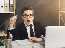 El pequeño hombre de negocios tiene gran idea en oficina fotografía de archivo