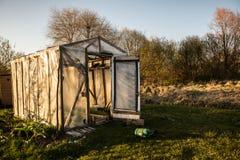 El pequeño invernadero con las puertas se abrió en un jardín en verano en el sol Fotos de archivo libres de regalías