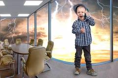 El pequeño jefe habla en su teléfono móvil Conversación emocional imagenes de archivo