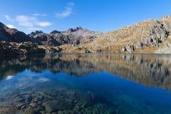 El pequeño lago de la montaña en Italia refleja las montañas Foto de archivo