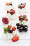 El pequeño merengue hecho en casa del pavlova se apelmaza con crema del mascarpone, fresas, cerezas y hojas de menta fresca Imágenes de archivo libres de regalías