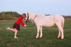 El pequeño modelo de una chica joven puso a su niño en un pequeño potro blanco fotografía de archivo libre de regalías