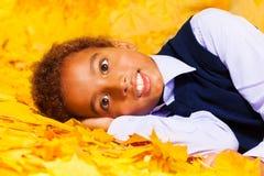 El pequeño muchacho africano pone en las hojas del amarillo del otoño Imagen de archivo libre de regalías